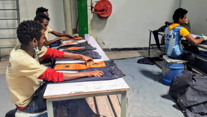 Lavoratori tagliano jeans. Image credit: Manjusha Nair
